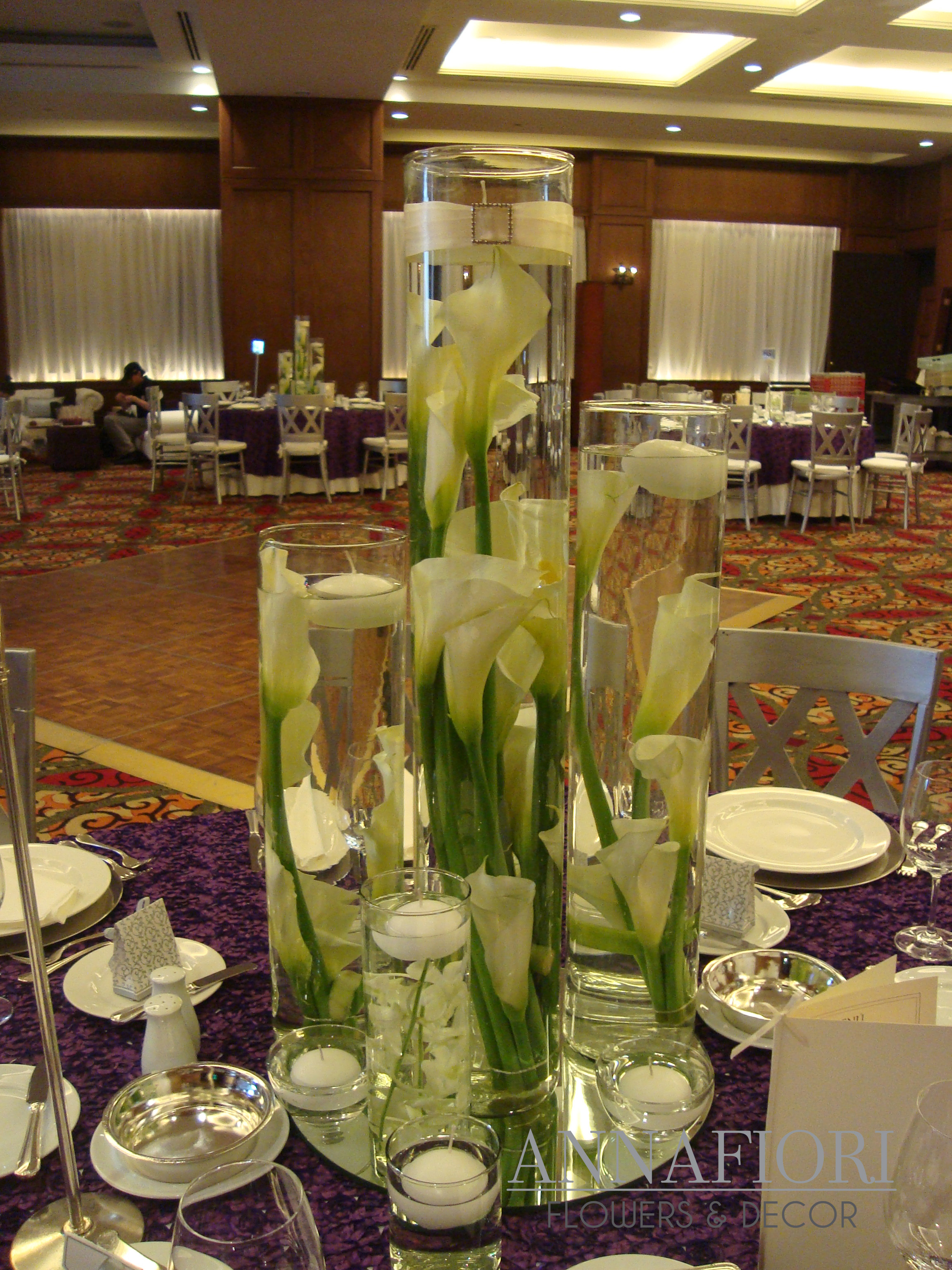 Centros de mesa con espejo y cilindros con velas flotantes